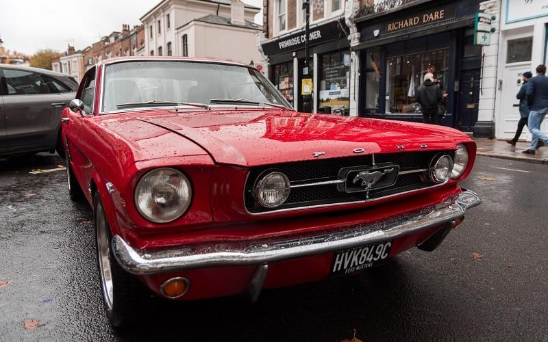 Red 1964-'66 Ford Mustang Coupe parked down the street on a rainy day