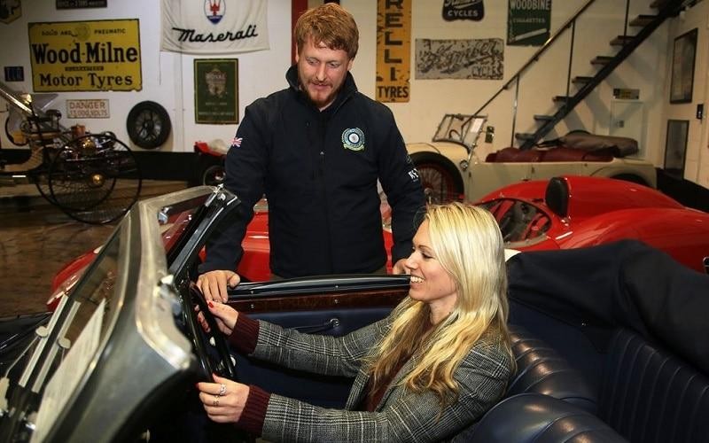 A woman sitting behind the wheel of a vintage car with a man standing beside the car in a vintage car gallery