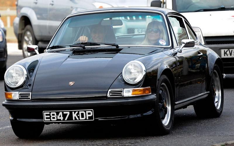 Jamie Hence and Kate Moss driving a classic Porsche 911 in the traffic