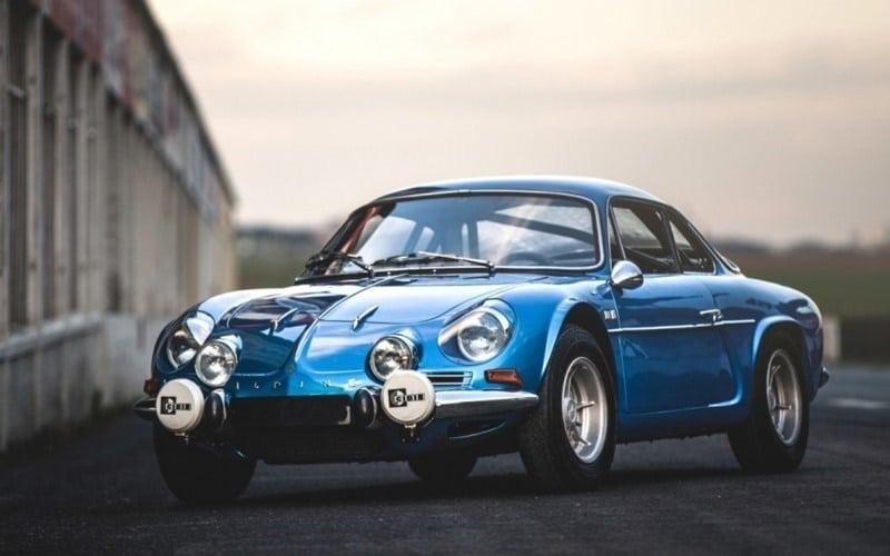 A metallic blue classic Alpine A110 parked at dusk