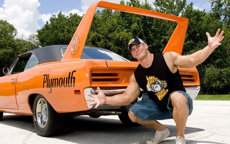 John Cena on his toes by his Plymouth Superbird's trunk
