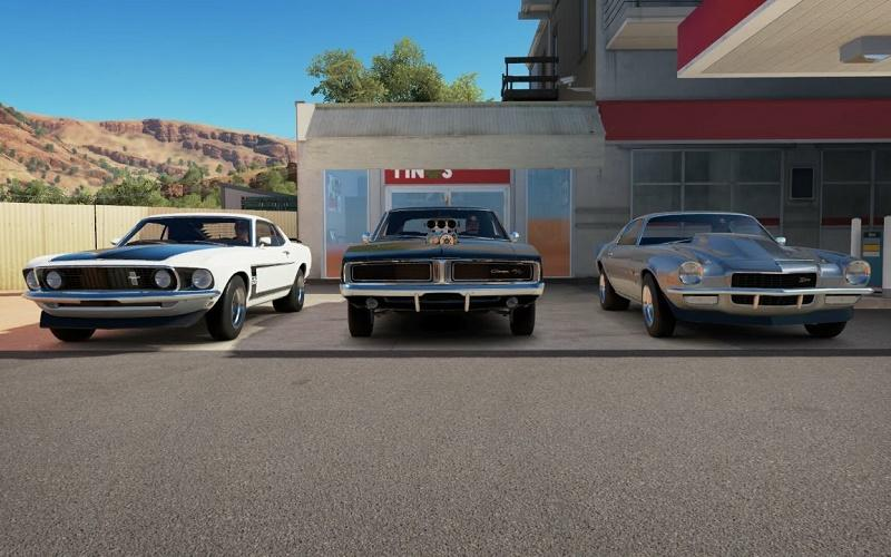 Graphic render of white 1969 Ford Mustang, black 1969 Dodge Charger, and silver 1970 Chevrolet Camaro parked side by side at a gas station