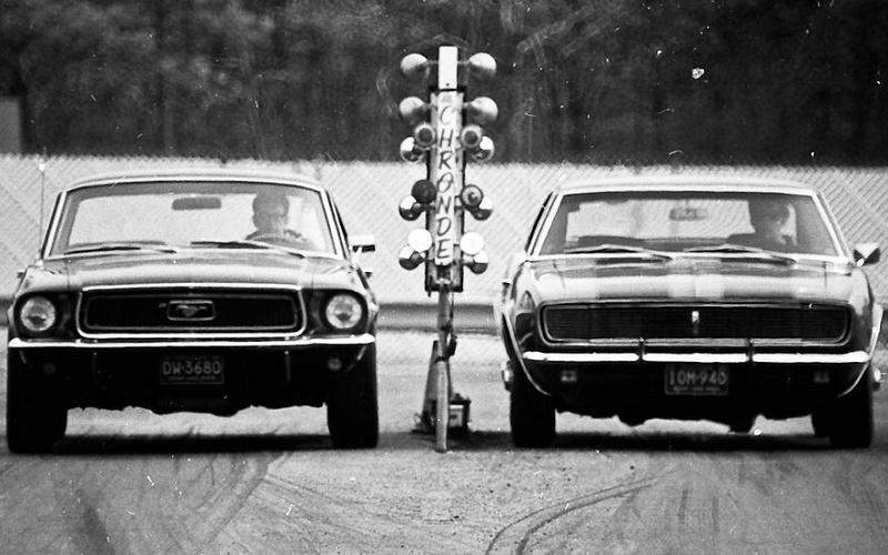 Black and white photo of '67-'68 Ford Mustang and '67-'68 Chevrolet Camaro at a drag race start line waiting for the green signal