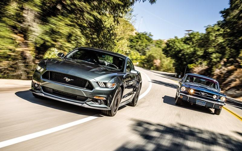 Two green Ford Mustangs of modern and classic generations while driving on the road